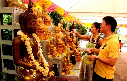 People cleansing Buddha statues with fragrant water