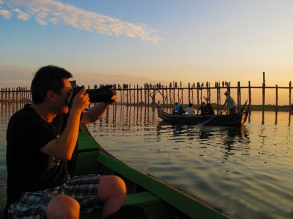 A tourist is photographing the beautiful sunset view of Ubein Bridge