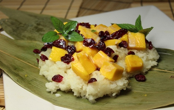 Irresistible greasy sticky rice served with slices of Thai fragrant mango