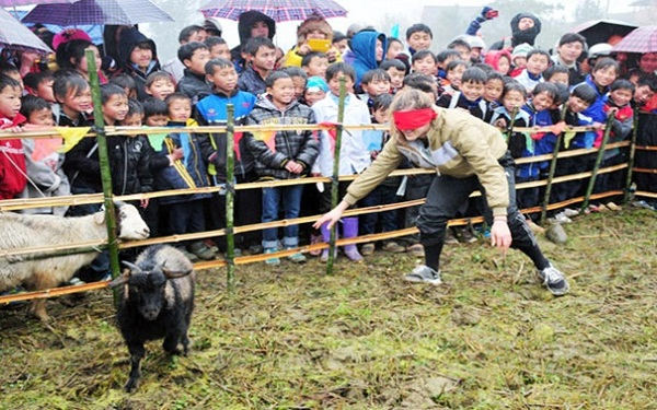 A forreign traveller playing catching a goat while blindfolded game