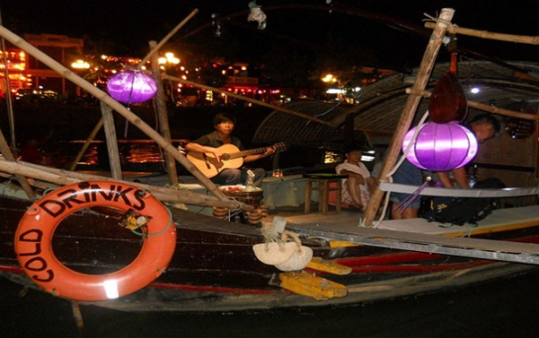 Step down a wooden boat on Hoai River where you can hear the melodic guitar