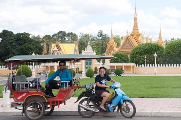 A tourist is trying to drive a tuk-tuk in Cambodia