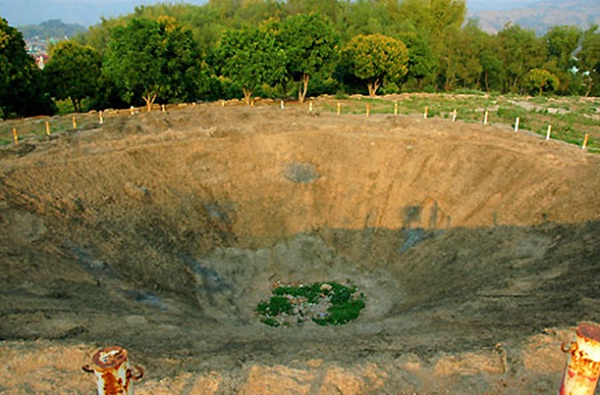 A huge hole marks the 1000 kilogram bomb explosion of  Viet Nam Army on A1 Hill in Dien Bien Phu