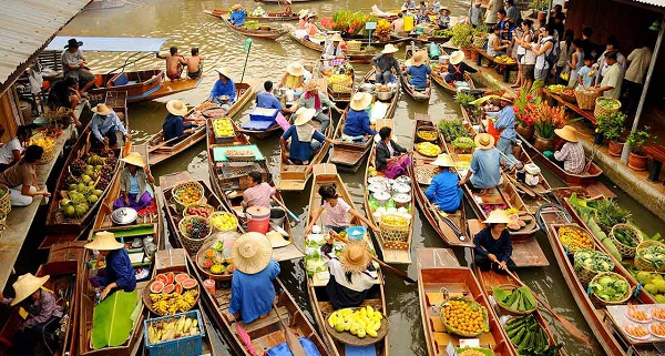 A crowded floating market in Bangkok selling many kinds of tropical fruits