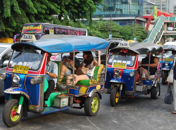 Tourists travel by tuk tuk in Thailand