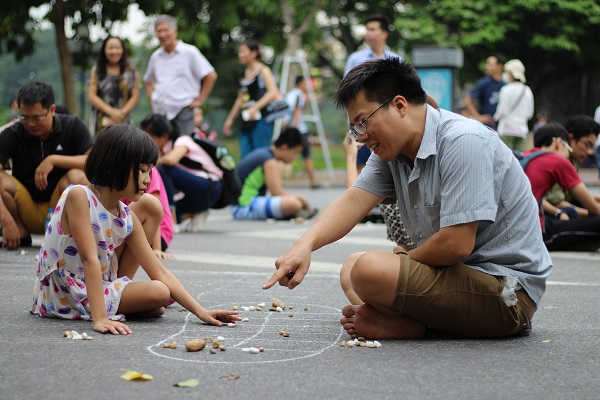 Playing Mandarin Square capturing - O an quan in Hoan Kiem lake on weekend