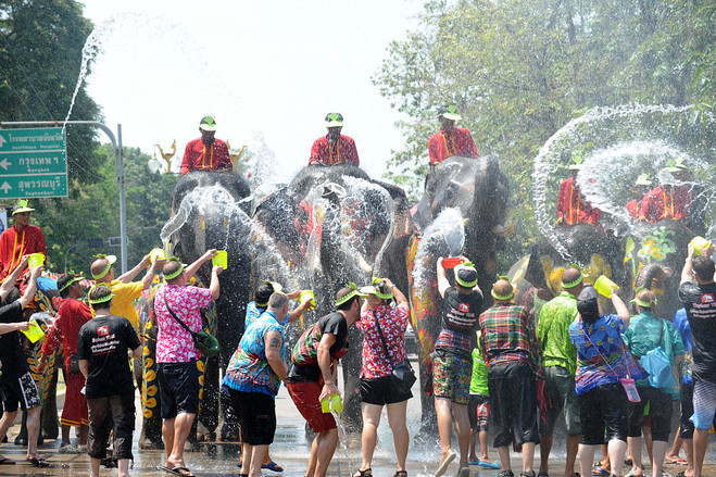 Local people and tourists splash water to each other happily