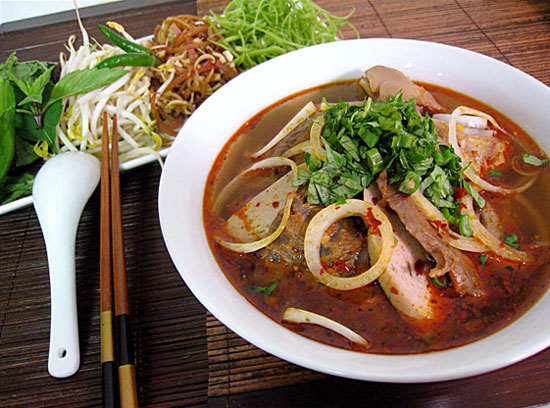 A bowl of Bun Bo Hue with bean sprouts, banana blossom, corianders and saw tooth herbs