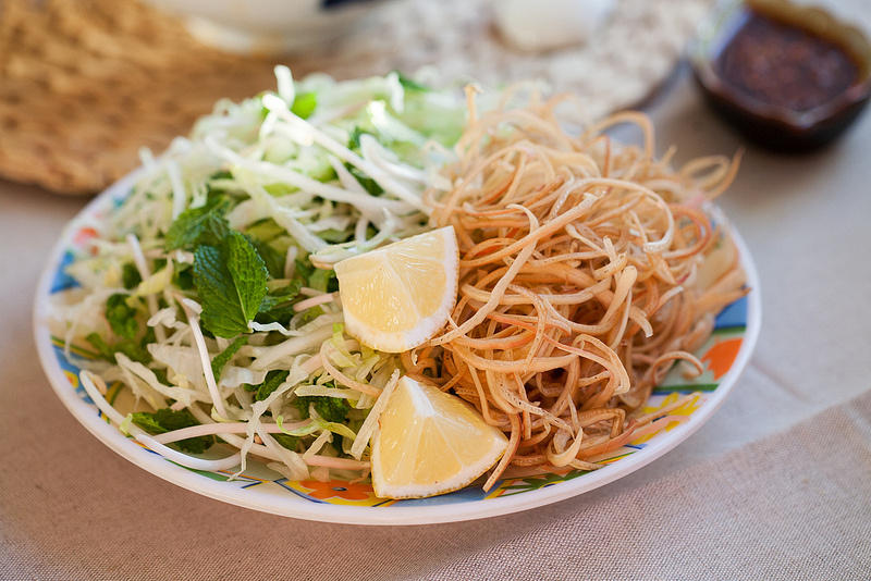 Bean sprouts, banana blossom, corianders, saw tooth herbs and lemon juice are usually eaten with Bun Bo Hue