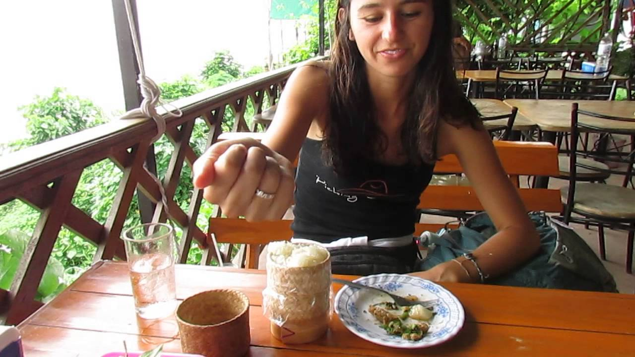 A beautiful girl is eating sticky rice by hand