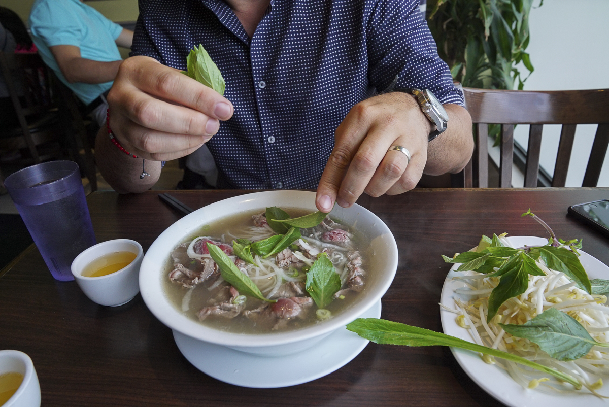 Tear herbs into the bowl of Pho