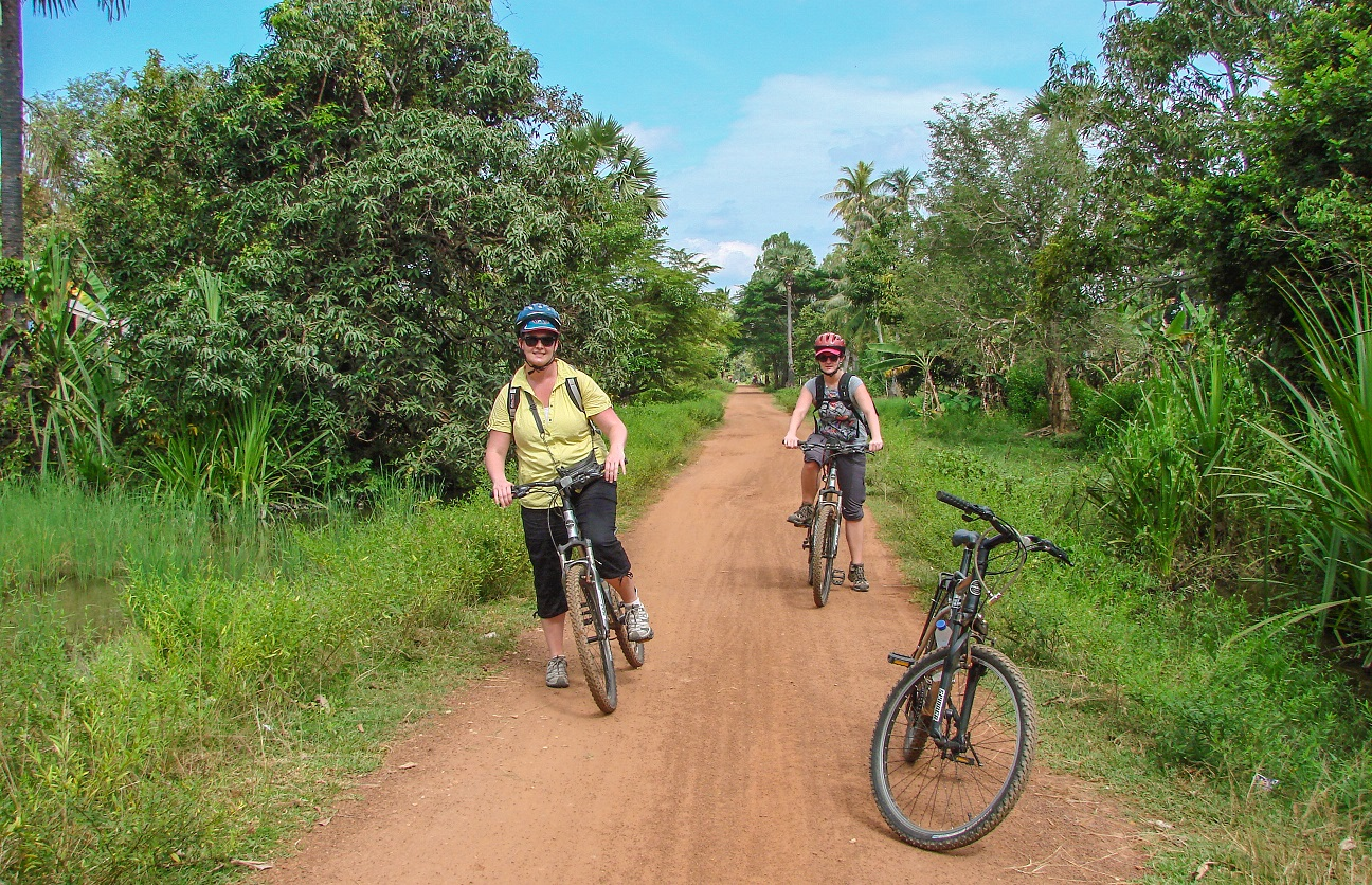 Travelers are riding bikes in a village in Siem Reap for sightseeing